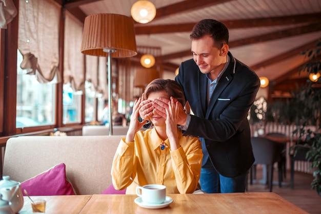 L'uomo felice chiude le mani degli occhi alla bella donna nel ristorante. appuntamento romantico di coppia d'amore