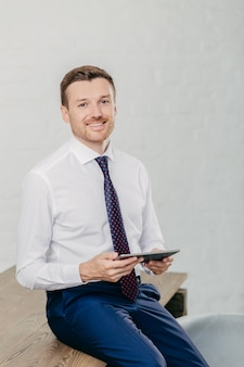 L'uomo felice in vestiti convenzionali controlla il email e legge la notifica sul computer moderno della compressa