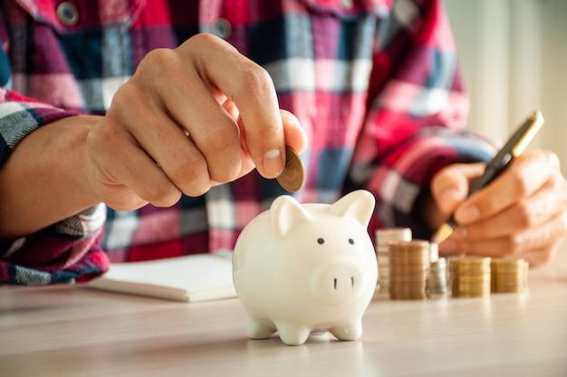 L'uomo felice mette i soldi in un porcellino salvadanaio