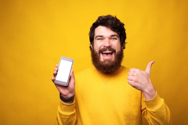 L'uomo felice mostra il pollice su o gradisce il gesto mentre tiene il suo telefono con lo schermo in bianco.