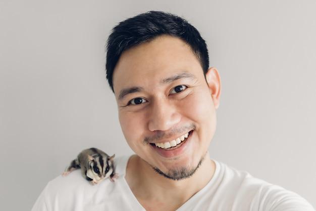 L'uomo felice sta prendendo selfie di se stesso e il suo animale domestico sugar glider.