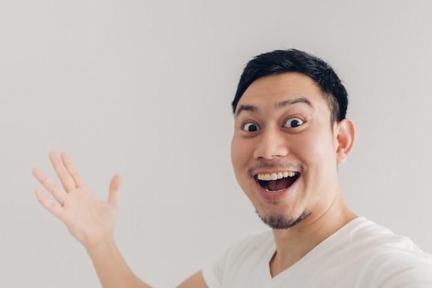 L'uomo felice sta prendendo selfie di se stesso e presenta lo sfondo vuoto dello spazio della copia.