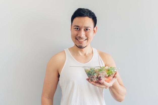 L'uomo felice sta presentando il pasto sano dell'insalata.