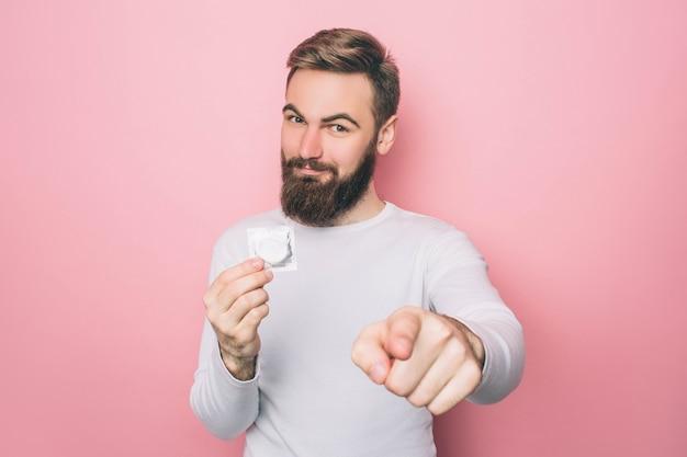 L'uomo felice sta tenendo un preservativo e sta indicando