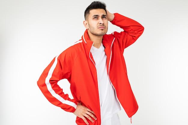 L'uomo forte in un vestito rosso di sport ha riflesso su una priorità bassa bianca con lo spazio della copia