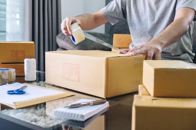 L'uomo freelance delle pmi che lavora con i loro imballaggi confeziona il mercato online delle consegne