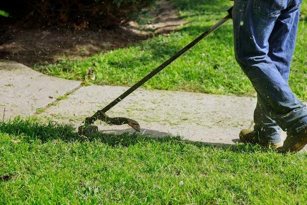 L'uomo giardiniere falcia l'erba con un tosaerba a mano in giornata di sole