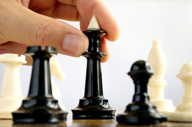 L'uomo gioca a scacchi e mostra la mano dei pezzi degli scacchi
