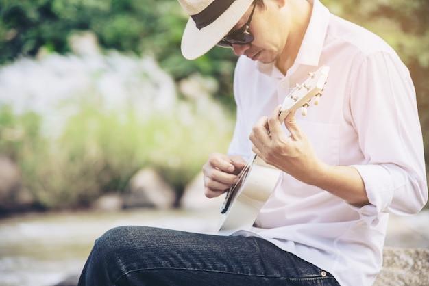 L'uomo gioca l'ukulele nuovo al fiume
