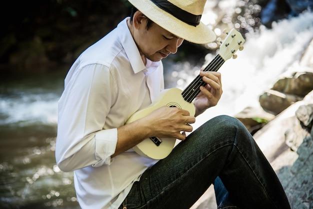 L'uomo gioca l'ukulele nuovo alla cascata