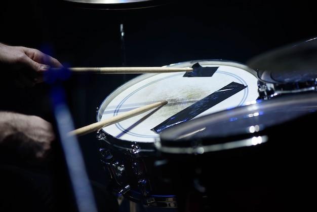 L'uomo gioca lo strumento di percussione musicale con il primo piano dei bastoni