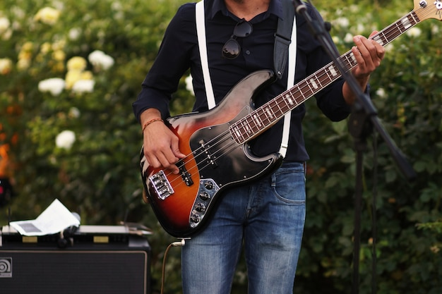 L'uomo gioca una chitarra in piedi nel giardino