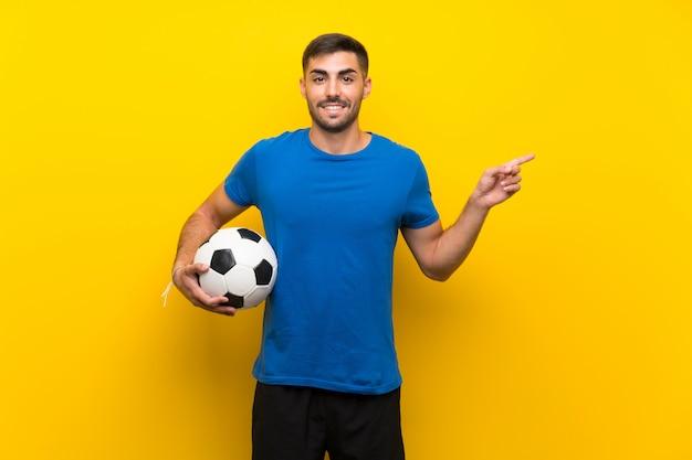 L'uomo giovane bello del giocatore di football americano sopra la parete gialla isolata ha sorpreso ed indicare il dito al lato