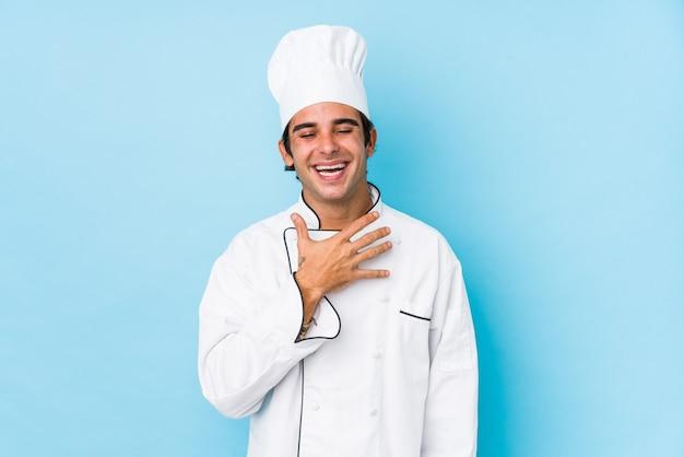 L'uomo giovane cuoco isolato ride ad alta voce tenendo la mano sul petto.