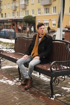 L'uomo giovane hipster si siede su una panchina, guarda lontano, in inverno fuori