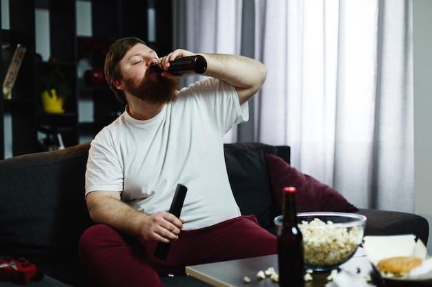 L'uomo grasso beve birra sdraiata sul divano