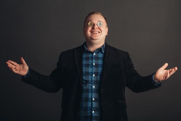 L'uomo grasso che celebra rende pazzo l'amante dei bitcoin con la moneta d'oro sugli occhi