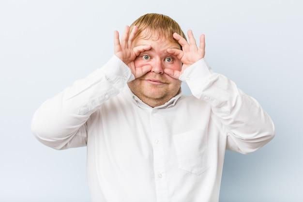 L'uomo grasso della giovane testarossa autentica che mostra okay firma sopra gli occhi