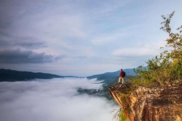 L'uomo guarda al mare di nebbia in alta montagna.