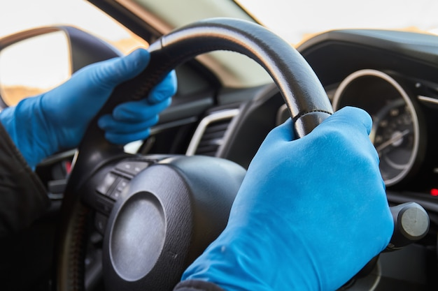L'uomo guida un'auto in guanti medici protettivi blu
