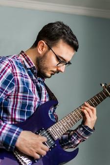 L'uomo impara a suonare la chitarra elettrica a casa