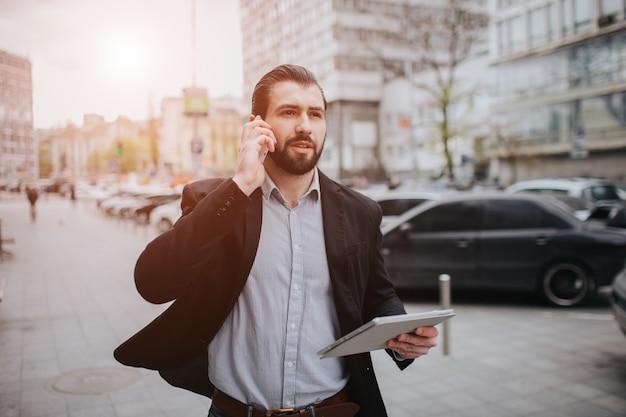 L'uomo impegnato ha fretta, non ha tempo, parlerà al telefono mentre è in movimento. uomo d'affari che fa più compiti. uomo d'affari multitasking.