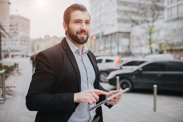 L'uomo impegnato ha fretta, non ha tempo, userà il tablet pc in viaggio. uomo d'affari che fa più compiti. uomo d'affari multitasking.