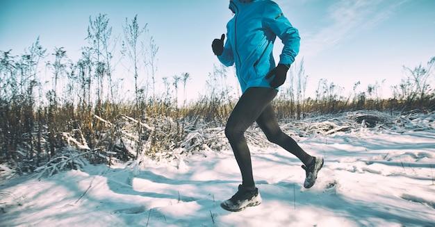 L'uomo in abbigliamento sportivo fa jogging attraverso le strade di campagna invernali coperte di neve