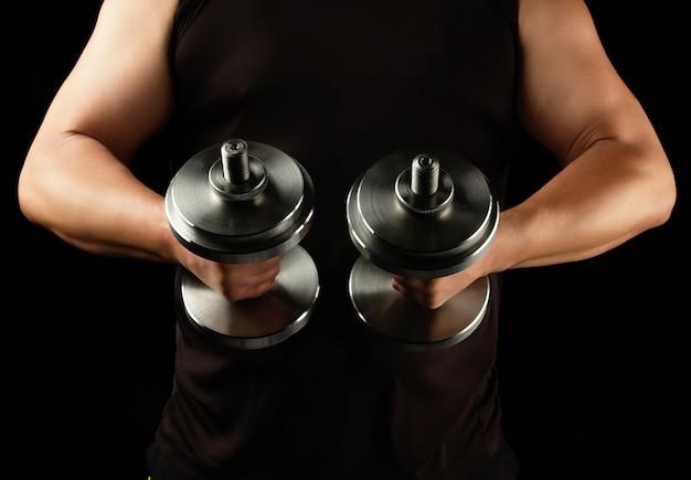 L'uomo in abiti neri tiene in mano manubri d'acciaio, i suoi muscoli sono tesi