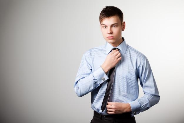 L'uomo in camicia blu raddrizza la cravatta