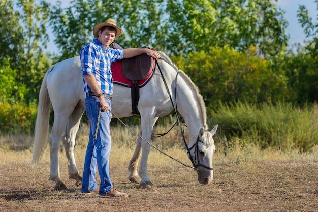 L'uomo in camicia e cappello cammina con un cavallo bianco