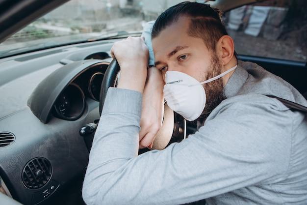 L'uomo in camicia e mascherina medica si siede al volante della macchina.