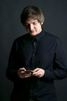 L'uomo in camicia nera controlla il suo iphone