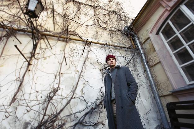 L'uomo in cappotto nero si leva in piedi sul cortile beige