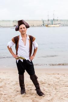 L'uomo in costume da pirata si mise le mani sui fianchi sulla spiaggia.