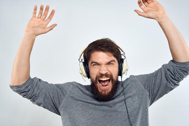 L'uomo in cuffia ascolta la luce del tempo libero di stile di vita di musica.