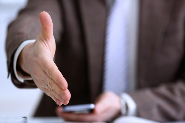 L'uomo in giacca e cravatta dà la mano come ciao in primo piano dell'ufficio. amico benvenuto mediazione offerta introduzione positiva grazie gesto vertice partecipazione approvazione motivazione contrattazione braccio maschio