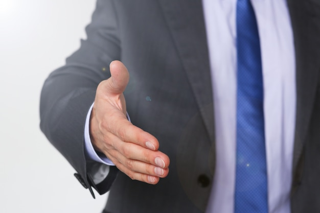 L'uomo in giacca e cravatta dà la mano come ciao in primo piano dell'ufficio