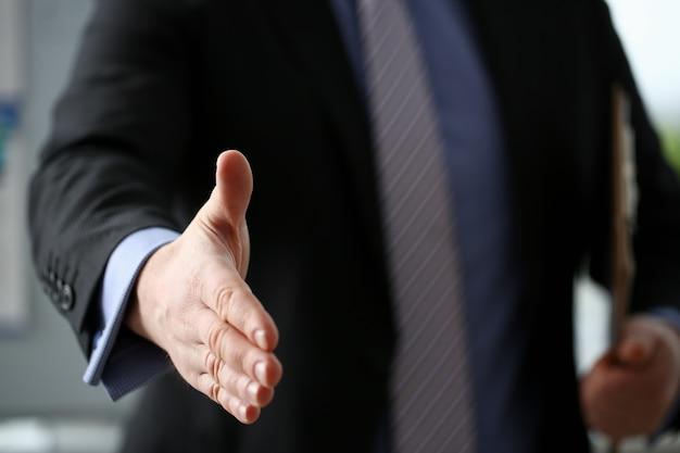 L'uomo in giacca e cravatta dà la mano come ciao