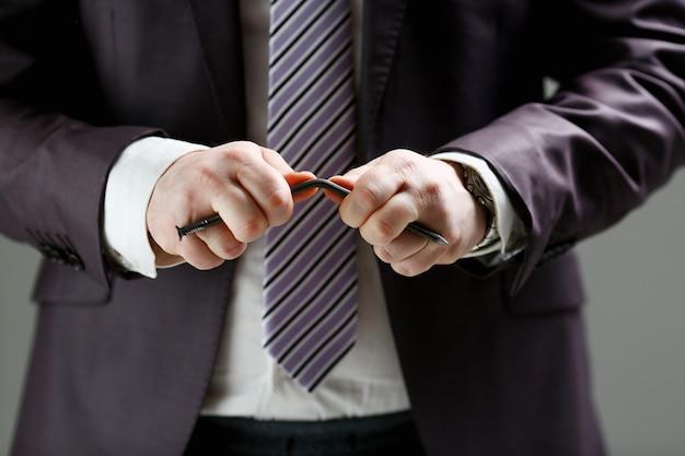 L'uomo in giacca e cravatta piega il chiodo con il primo piano delle armi