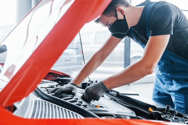 L'uomo in maschera protettiva uniforme e nera lavora con l'automobile rotta. concezione del servizio auto