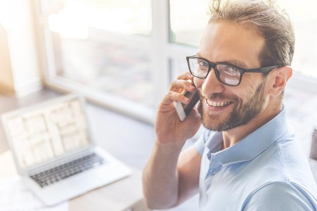 L'uomo in occhiali sta parlando al telefono cellulare