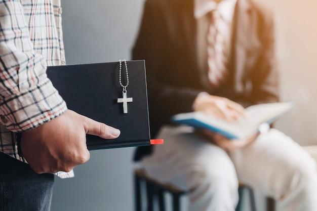 L'uomo in piedi condivide il vangelo nella bibbia con l'uomo. equipaggi le dita che indicano alle lettere all'interno della bibbia. il concetto di cristianesimo.
