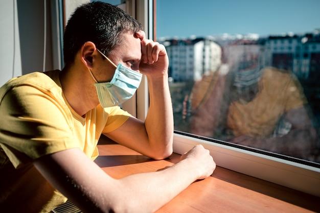 L'uomo in quarantena a causa di un virus si siede a casa in una maschera e guarda fuori dalla finestra in una giornata di sole. concetto di coronavirus. covid-19