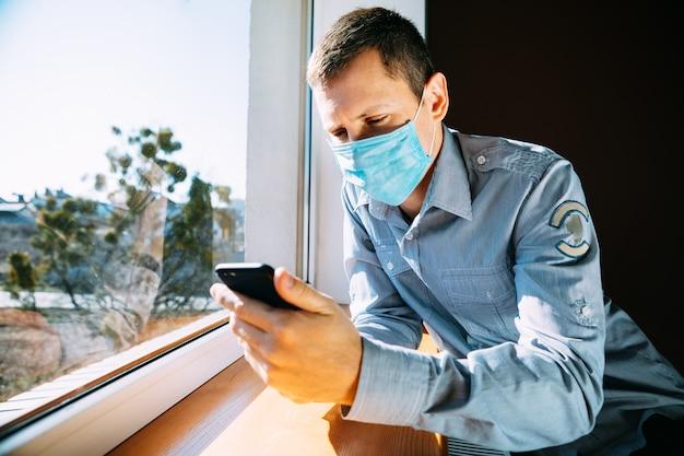 L'uomo in quarantena a causa di un virus si siede a casa in una maschera e guarda fuori dalla finestra in una giornata di sole.