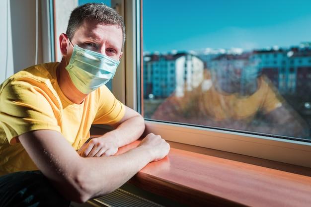 L'uomo in quarantena si siede a casa in una maschera e guarda fuori dalla finestra in una giornata di sole. concetto di coronavirus.