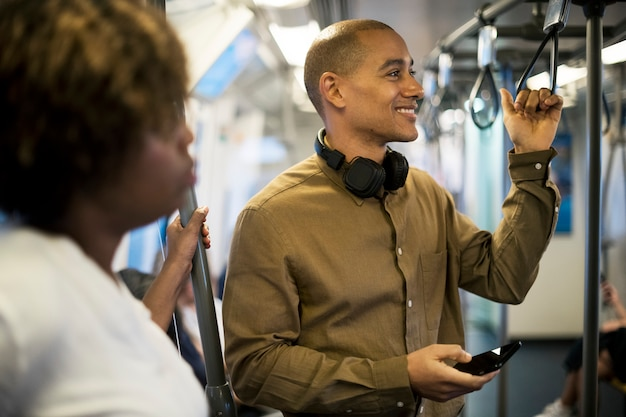 L'uomo in sella a un treno e tenendo il suo smartphone