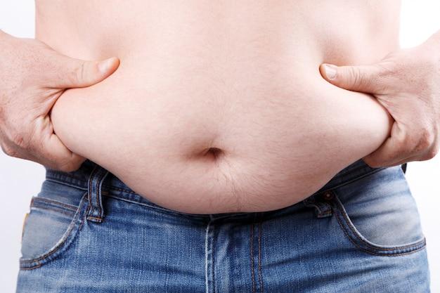 L'uomo in sovrappeso detiene le sue pieghe grasse