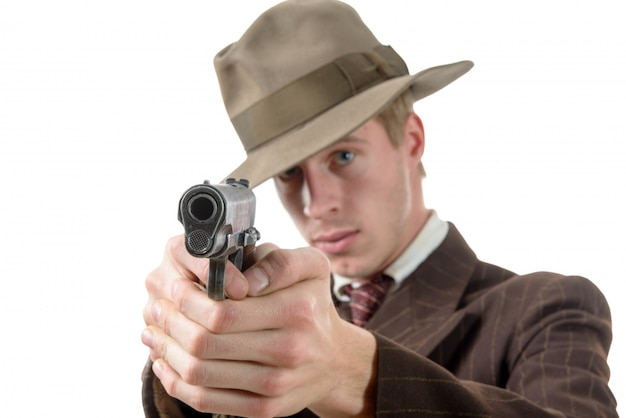 L'uomo in un'annata del vestito, mira con una pistola, su bianco