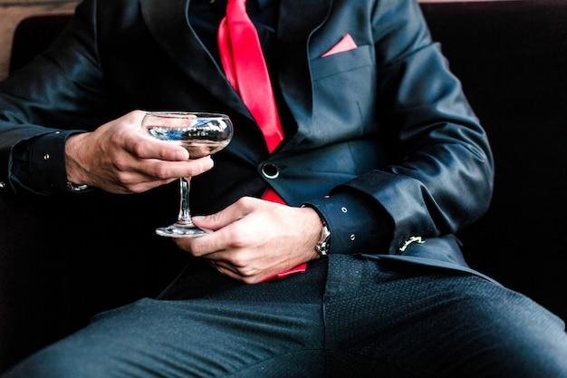 L'uomo in un vestito si siede e beve un cocktail